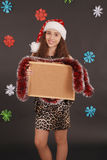 Young christmas girl in santa hat with blank cork board Stock Photo
