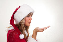 Young Christmas Woman is blowing snow. Young woman, dressed in a Christmas costume is blowing snow Stock Photos