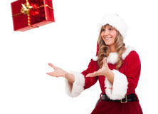 Young Christmas Woman is catching an xmas present. Young woman, dressed in a Christmas costume is catching an xmas present Royalty Free Stock Photography