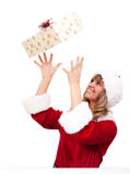 Young Christmas Woman is catching an xmas present. Young woman, dressed in a Christmas costume is catching an xmas present Royalty Free Stock Image