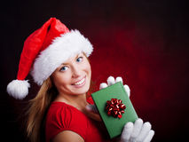 Young christmas woman holding present over dark Royalty Free Stock Images