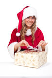 Young Christmas Woman is opening an xmas present. Young woman, dressed in a Christmas costume is opening an xmas present Royalty Free Stock Images