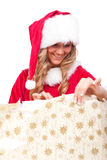 Young Christmas Woman is opening an xmas present. Young woman, dressed in a Christmas costume is opening an xmas present Stock Images