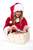 Young Christmas Woman is opening an xmas presents. Young woman, dressed in a Christmas costume is opening an xmas presents Stock Image