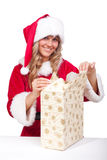Young Christmas Woman is opening an xmas presents. Young woman, dressed in a Christmas costume is opening an xmas present Stock Photos