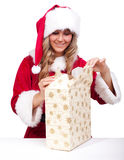 Young Christmas Woman is opening an xmas presents. Young woman, dressed in a Christmas costume is opening an xmas present Stock Photography