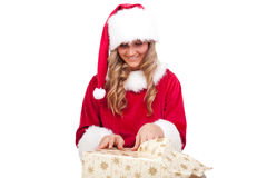 Young Christmas Woman is opening an xmas presents. Young woman, dressed in a Christmas costume is opening an xmas present Royalty Free Stock Photography