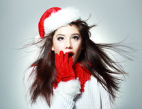 Young christmas woman. Christmas santa woman surprised. Beautiful face of happy asian woman in santa hat Stock Photos