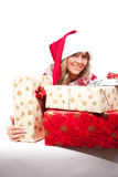 Young Christmas Woman with some presents. Young woman, dressed in a Christmas costume. She is holding some presents in her hands Royalty Free Stock Photography