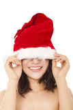 Young christmas woman using santa cap to cover eyes. Royalty Free Stock Photo