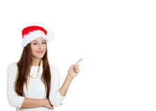 Young christmas woman wearing red santa claus hat pointing with index finger to space at right Royalty Free Stock Photo
