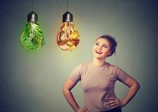 Woman thinking of diet choice. Young chubby girl looking up at light bulbs with green salad and junk food making choice in diet royalty free stock photography