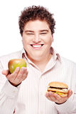 Young chubby man holding apple and hamburger Stock Image
