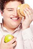 Young chubby man holding apple and hamburger Stock Photography