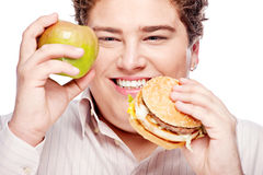 Young chubby man holding apple and hamburger Royalty Free Stock Photo