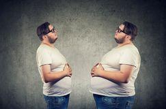 Young chubby man looking at fat himself feeling bloated. stock photos