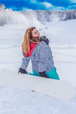 Young chubby woman with a snowboard on the ski slopes, kneeling in the snow Stock Photo