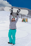 Young chubby woman in winner attitude, raises your snowboard in the air. Royalty Free Stock Photo
