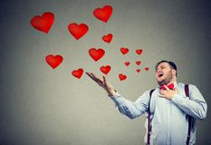 Young man having love tragedy. Young chunky man screaming being hurt with love while posing on gray backdrop Royalty Free Stock Photography