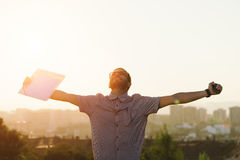 Young city professional man success. Successful professional casual man celebrating work success and raising arms against city background on sunset. Job stock photos