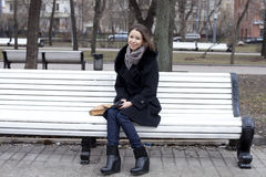 Young city woman sits on a bench Royalty Free Stock Photos