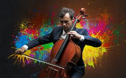 Composer with splotch and his cello. Young classical musician with colorful splotch wallpaper stock photography