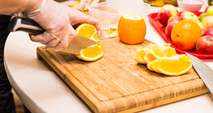 Young clean chef hands cutting orange on  table Royalty Free Stock Images