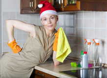 Young cleaning lady in the kitchen. In a Santa Claus hat royalty free stock photo