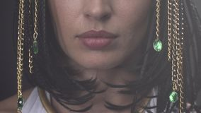 Close up of the lips of Cleopatra, with some jewelry hanging from her hair. Young Cleopatra with black hair and some jewelry gold chains with green gems hanging stock video
