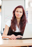 Young clerk. Female clerk with laptop sitting in office Stock Photos