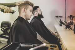 Young clients having their hair cut by hairdressers. Young positive efficient clients having their hair cut by hairdressers at salon royalty free stock image