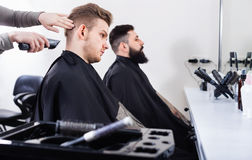 Young clients having their hair cut by hairdressers. Young smiling efficient clients having their hair cut by hairdressers at salon Royalty Free Stock Photos