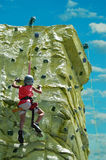Young Climber. A young boy climbing to his goal on a rock wall Stock Image