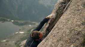 Young climber climbing a high mountain. stock footage