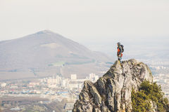 A young climber looking out of the top of a steep cliff against the background of caucasian city and mountains. A young climber looking out of the top of a steep Royalty Free Stock Photos