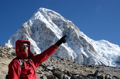 Young climber standing near Kala Patthar mountain and showing to Everest summit,Nepal stock photo