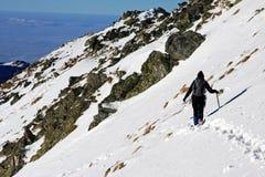 Young climber trekking through deep snow in Retezat mountains, Romania Stock Photography