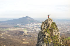 A young climber winds the rope to the tops of a steep cliff against the backdrop of the city and the caucasian mountain. A young climber winds the rope to the Royalty Free Stock Photography