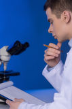 Young clinician studying chemical elements in laboratory. Stock Photos