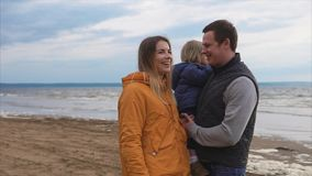 Young close-knit family with little daughter by the sea. Family couple with little daughter at the beach, sea background. Sincere happiness of being together stock footage