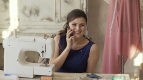 Young clothing designer and seamstress woman near sewing machine talks phone smiling in studio stock footage