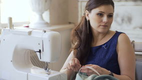 Young clothing designer and seamstress woman work with sewing machine in tailor studio stock video footage