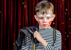 Young Clown Looking Sad on Stage. Head and Shoulders of Young Boy Wearing Clown Make Up Holding Leather Jacket Over Shoulder and Looking Solemnly Downward on stock photography