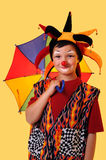 Young Clown With Umbrella. Portrait of young clown with umbrella over a yellow background Royalty Free Stock Image