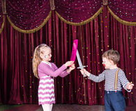 Young Clowns Having Prop Sword Fight on Stage Royalty Free Stock Photography