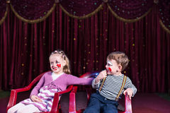 Young Clowns Sitting and Laughing on Stage Stock Photo