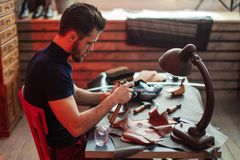Young cobbler repairing a shoe with a hammer. Close up side view photo royalty free stock photo