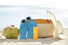 Young coconut, flipflops, sunglasses, bag, sunblock, and hat on. Portrait of young coconut, flipflops, sunglasses, bag, sunblock, and hat on sand for summer Royalty Free Stock Photography