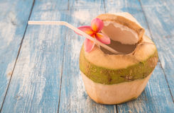 Young coconut,Plumeria on blue wooden floor. Royalty Free Stock Images