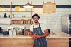 Young coffee shop owner standing at the counter Stock Images